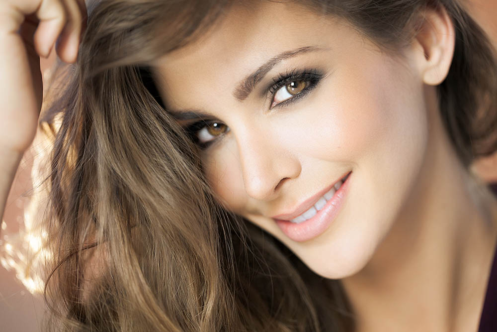 A closeup portrait of a young happy woman with beautiful eyes. Fashion and beauty concept in studio.