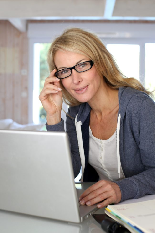 13904623 - middle-aged blond woman working at home with laptop