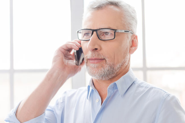 Tell me good news! Serious grey hair senior man in shirt talking on the mobile phone and looking away while standing in front of the window